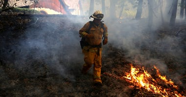 : A CalFire chief runs past burning grass during a firing operation while battling the Tubbs Fire on October 12, 2017 near Calistoga, California.