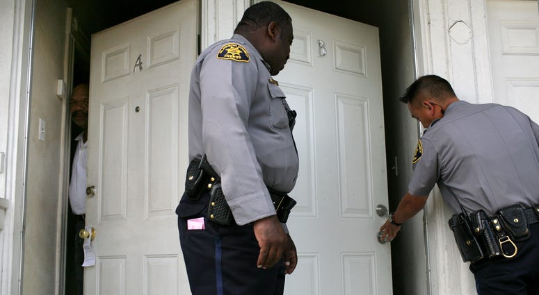 A neighbor peers out of his door as Alameda County Sheriff deputies Ken Cammack (C) and Ken Kong (R) enter an apartment to evict tenants who have defaulted on rent payments June 4, 2009.