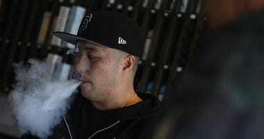 Jeremy Wong blows vapor from an e-cigarette at The Vaping Buddha on January 23, 2018 in South San Francisco, California.