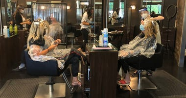Stylists wear shields and PPE in working with clients at this salon in Walnut Creek.