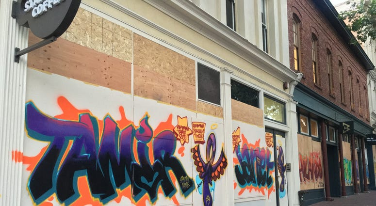Graffiti honoring other Black lives lost to police on boarded up storefronts in downtown Oakland, June 3, 2020