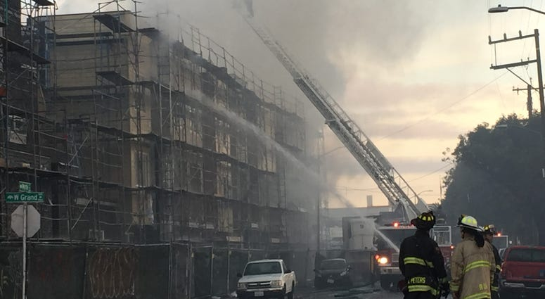A fire at a luxury condo project in West Oakland was spread by embers to nearby buildings.