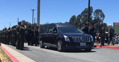 Sgt. Damon Gutzwiller's hearse gets one final salute.