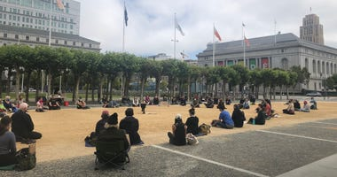 A group of about 100 people sits and meditates in front of City Hall in San Francisco.