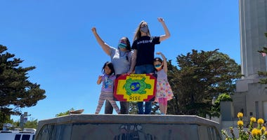 Mariposa Villaluna (left), Amy Anderson (right) and their kids celebrate the removal of San Francisco's Christopher Columbus statue.