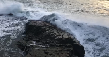 This image shows a man at Bonny Doon Beach moments before he was knocked into the ocean by a wave. Park workers in Santa Cruz rescued the man, according to a video released by county officials.
