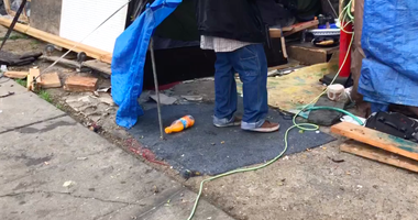 A homeless camp along 12th Street in Oakland has many residents who have tapped into light poles and other sources of electricity.