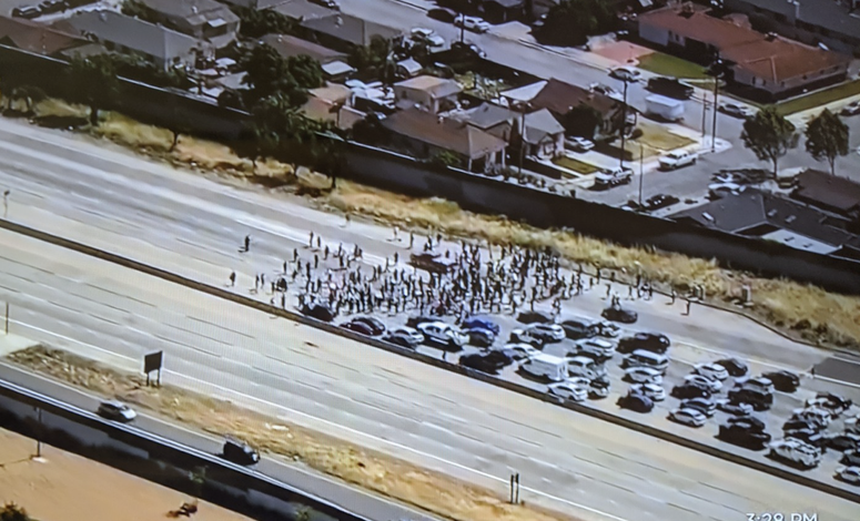 An overhead view of a protest on Highway 101 in San Jose, stopping traffic in both directions.