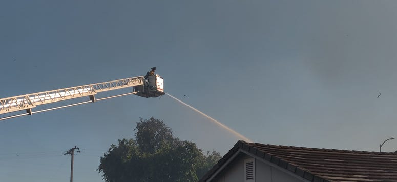 A firefighter douses a house in Suisun City during a marshland fire.