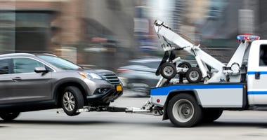 A tow truck hauls a car.