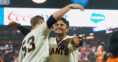 San Francisco Giants second baseman Donovan Solano (7) hugs right fielder Austin Slater (53) after hitting a walk-off single against the New York Mets during the sixteenth inning at Oracle Park on July 18, 2019.