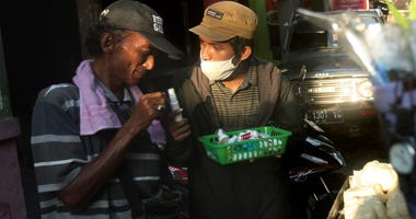 Students provide sanitizers to daily workers to fight virus