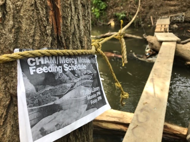 A flier posted by CHAM Deliverance Ministry volunteers on a tree next to San Jose's Coyote Creek to inform those who live in nearby homeless encampments when food distributions will take place