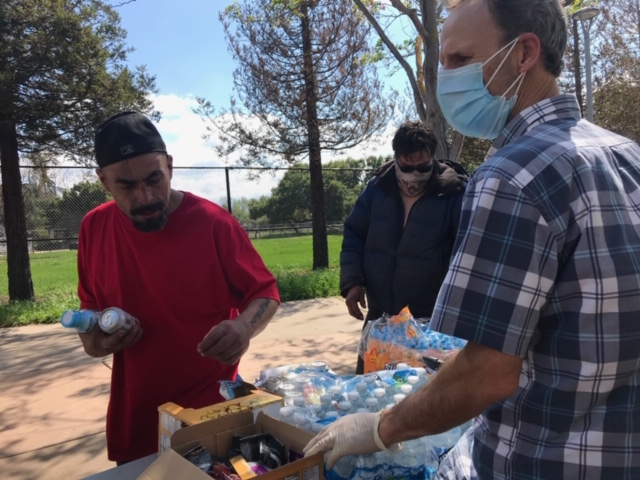 CHAM Deliverance Ministry volunteer Rick Crawford manning the food table during a distribution to homeless residents living near the Tully Community Branch Library in San Jose
