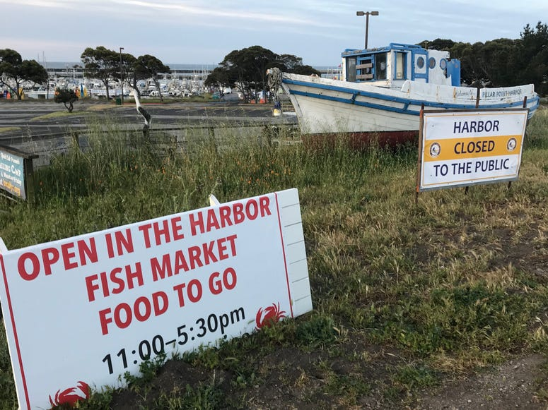Conflicting signs at Pillar Point Harbor in Half Moon Bay, which has closed due to coronavirus
