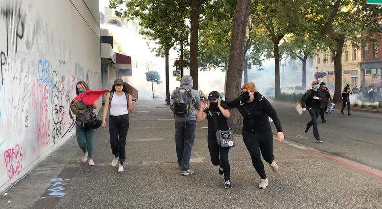 Protestors run as tear gas is deployed in Oakland, 6-1-20