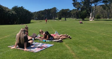 People relax at the Presidio Golf Course, which has closed to golfers and opened for hiking, walking and biking