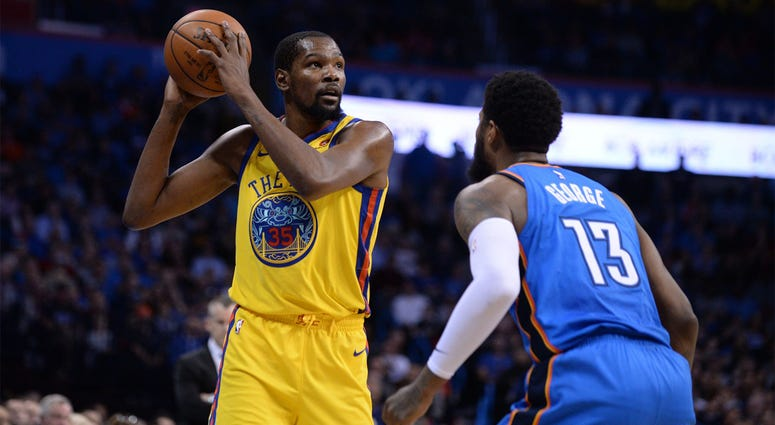 Apr 3, 2018; Oklahoma City, OK, USA; Golden State Warriors forward Kevin Durant (35) handles the ball in front of Oklahoma City Thunder forward Paul George (13) during the second quarter at Chesapeake Energy Arena. Mandatory Credit: Mark D. Smith-USA TODA