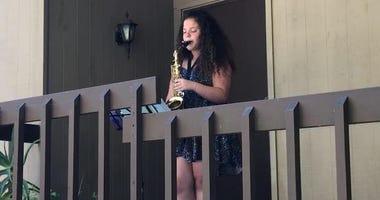 Oakland teenager Grace Gulli plays her saxophone for neighbors