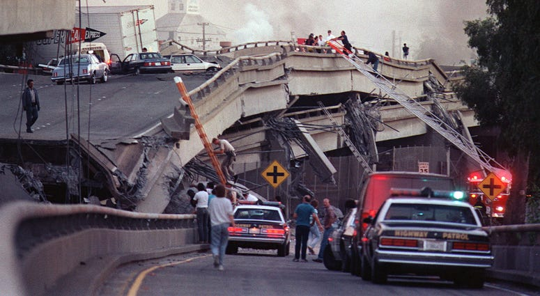 Rescue workers and police enter the scene of destruction where the Interstate 880-Interstate 80 interchange collapsed in Oakland during the Loma Prieta earthquake in October 1989.