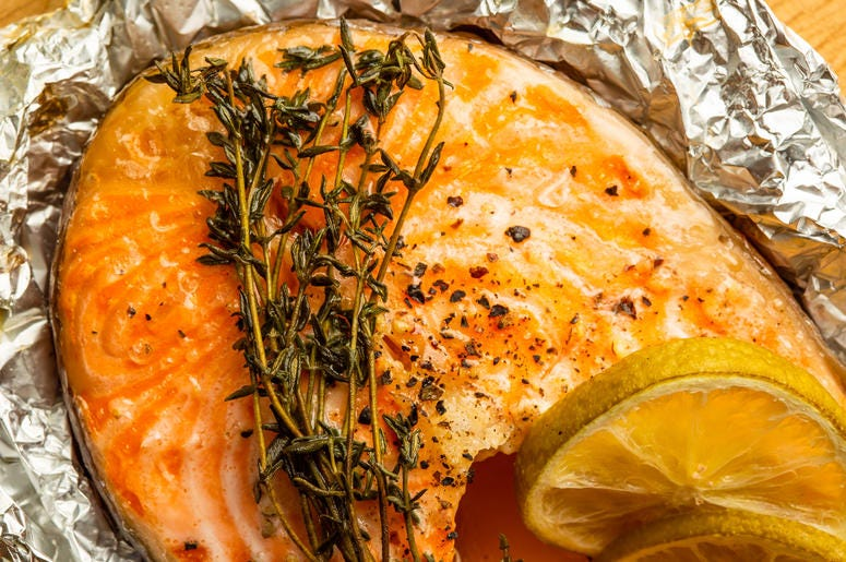 Branch of thyme on the top of baked fish in foil - stock photo Close up of the green branch of thyme and two slices of lime placed on the top of baked fish in foil
