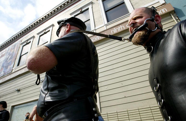 "A man who did not want to be identified by name pulls his slave ""Ricky"" at the 20th Annual Folsom Street Fair September 28, 2003 in San Francisco, California."