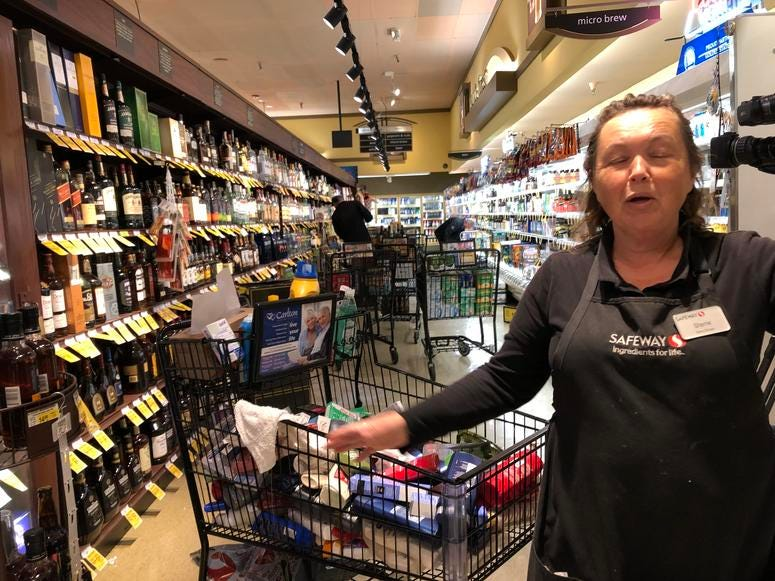 Safeway Bakery Manager Sherrie Blaine helps clean up in the supermarket after products fell from the shelves during a 4.5 magnitude earthquake on Oct. 14, 2019.