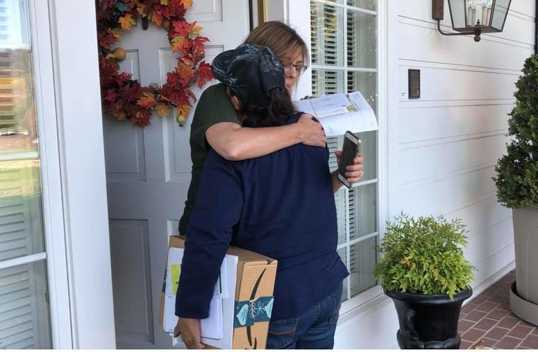 Postal worker Bernadette Laos embraces a customer on her route in Sonoma County. Laos' home was destroyed by the Kincade Fire.