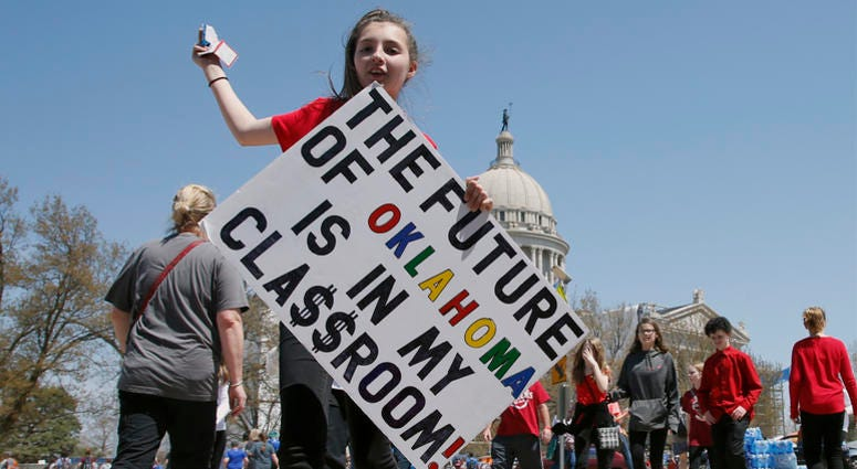 Trinity Redford, 13, of Blackwell, Okla., walks from the state Capitol with a protest sign as protests continue over school funding at the state Capitol in Oklahoma City, Thursday, April 12, 2018. (AP Photo/Sue Ogrocki)
