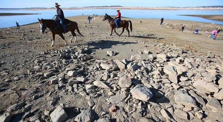 Folsom police Officers Eric Baade, left, and Daren Prociw, right, of the mounted enforcement detail, ride their horses across the exposed lake bed at Folsom Lake, Jan. 21, 2014 in Folsom, Calif.