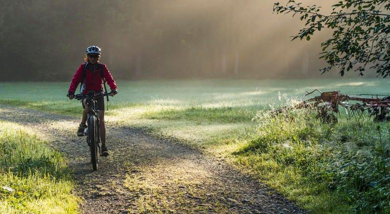 A woman rides an e-bike along a nature trail