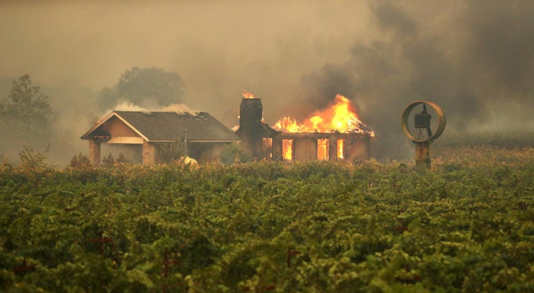 4: A home burns near a vineyard after the Kincade Fire burned through the area on October 24, 2019 in Geyserville, California.