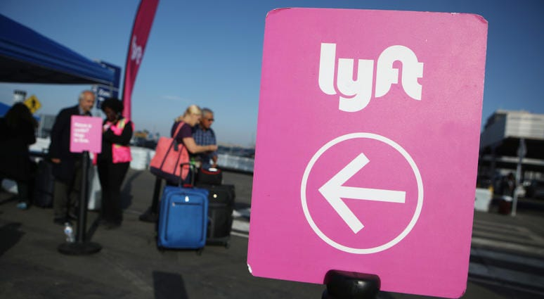 Arriving passengers wait to board Lyft vehicles at the new 'LAX-it' ride-hail passenger pickup lot at Los Angeles International Airport (LAX) on November 6, 2019.