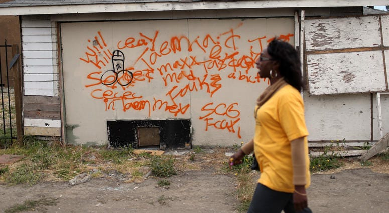 A member of the Richmond, California chapter of the Alliance of Californians for Community Empowerment (ACCE) walks by an abandoned garage during a bus tour of foreclosed and blighted properties on July 13, 2012 in Richmond, California.