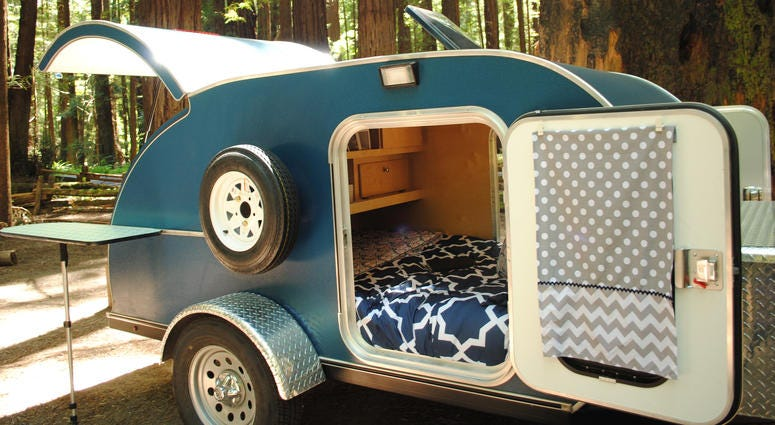 Blue teardrop camping trailer with doors open and view to interior, setup at a campsite surrounded by redwood trees in Humboldt Redwoods State Park in California.