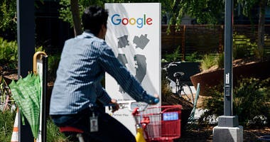 : People ride bikes past signage on the Google campus as Google workers inside hold a sit-in to protest sexual harassment at the company, on May 1, 2019 in Mountain View, California.