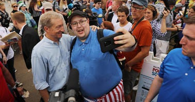Democratic presidential candidate Tom Steyer (L), a billionaire hedge fund manager and activist, poses for a selfie at the Iowa State Fair August 11, 2019 in Des Moines, Iowa.