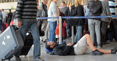 : A passenger takes a nap as other passengers wait in line for Lufthansa flights on October 20, 2014 in Frankfurt am Main, Germany