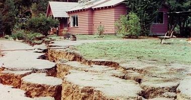 The force of the October 1989 Loma Prieta earthquake opened these large fissures in the ground in front of this home on Summit Road in the Santa Cruz mountains in Santa Cruz, CA