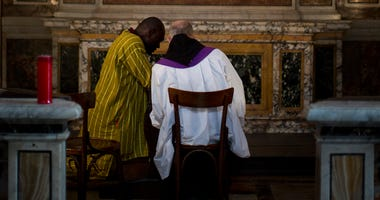 a Roman catholic priest listens to a man's confession