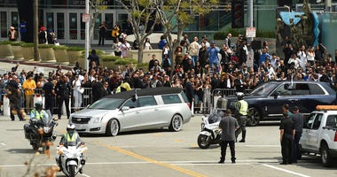 A silver hearse carrying the body of Nipsey Hussle, whose given name was Ermias Asghedom, leaves Staples Center in a procession following the Celebration of Life memorial service for the late rapper on Thursday, April 11, 2019, at the Staples Center in Lo