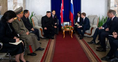 North Korea's leader Kim Jong Un, background, centre left, talks with Russian Minister for the development of the Russian Far East Alexander Kozlov