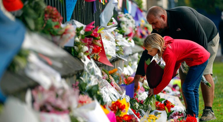 Mourners lay flowers on a wall at the Botanical Gardens in Christchurch, New Zealand, Saturday, March 16, 2019.