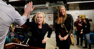 Democratic presidential candidate Sen. Kirsten Gillibrand, D-N.Y., high-fives a foosball opponent as partner Casey Leach of Manchester, N.H., laughs at a campaign meet-and-greet, Friday, March 15, 2019, at To Share Brewing in Manchester, N.H