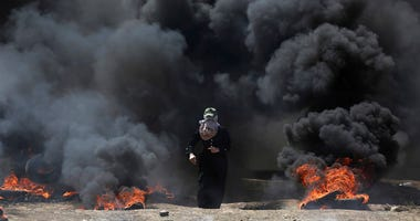 A Palestinian woman walks through black smoke from burning tires during a protest on the Gaza Strip's border with Israel,