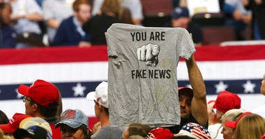 "a Trump supporter holds up a T-shirt reading ""You Are Fake News"""