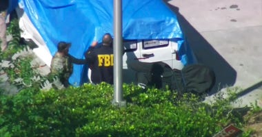 In this frame grab from video provided by WPLG-TV, FBI agents cover a van parked in Plantation, Fla., on Friday, Oct. 26, 2018In this frame grab from video provided by WPLG-TV, FBI agents cover a van parked in Plantation, Fla., on Friday, Oct. 26, 2018