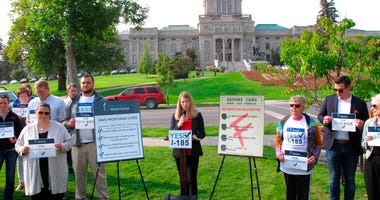 photo, Amanda Cahill of the American Heart Association speaks to a rally in support of a ballot initiative to raise the state's tobacco taxes in Helena, Mont