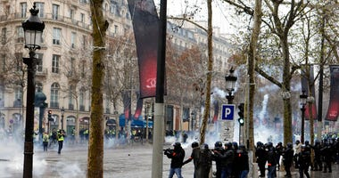 Riot police officers fire tear gas during scuffles on the Champs-Elysees avenue, Saturday, Dec. 15, 2018 in Paris.