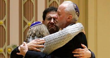 Rabbi Jeffrey Myers, right, of Tree of Life/Or L'Simcha Congregation hugs Rabbi Cheryl Klein, left, of Dor Hadash Congregation and Rabbi Jonathan Perlman